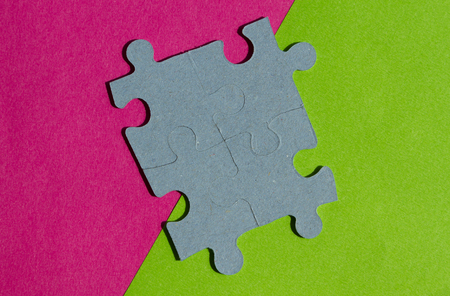 Jigsaw Puzzle pieces on border between pink and green background with copy space Stock Photo