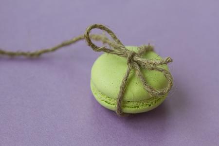 Maccherone verde con arco da corda naturale su sfondo viola, vista macro