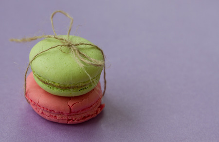 Two macaroons with bow from natural rope on purple background with copy space