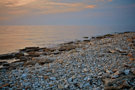 Seascape view. Rocky beach inSeascape view. Rocky beach in evening. Pebble shore. Tinted photo. evening. Pebble shore.