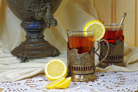 Russian samovar, tea with lemon in faceted glasses with cup holders. Tinted photo in vintage style. Stock Photo