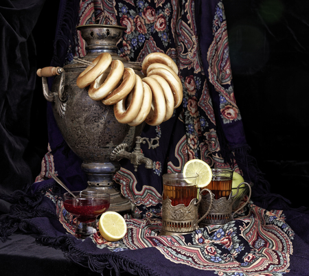 Russian samovar, tea with lemon in faceted glasses with cup holders and bublik. Tinted photo in vintage style on black background.