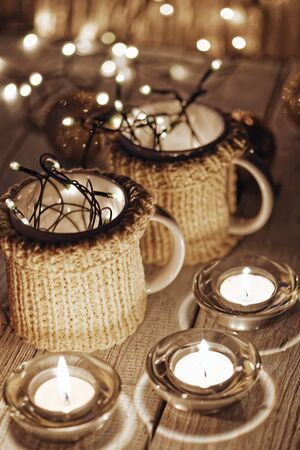 Ceramic stylish cups in sweaters and christmas retro garland on bokeh lights background. Shallow depth of field. Tinted photo.