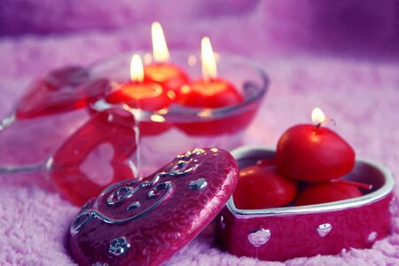 Porcelain box, lolipops and candles in the form of hearts on a pink background. Romantic concept of Valentines Day. Tinted photo