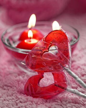 Lolipops and candles in the form of hearts on a pink background. Romantic concept of Valentines Day. Tinted photo
