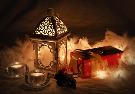 Close up of Xmas lantern with candles and gift. Christmas decoration on white fur. Shallow depth of field and bokeh