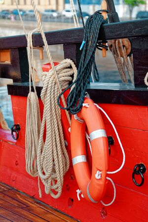 Close up of a rope and lifebuoy on a old wooden ship. Details deck of the saiilboat. Stok Fotoğraf