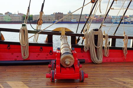 Historical cannon of an old wooden sailboat. Details deck of the ship