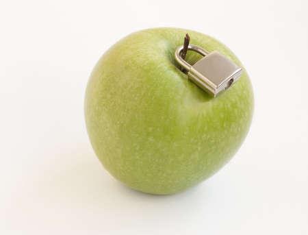 Green apple with metal padlock, concept photo
