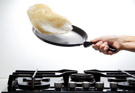 Koekenpan met vliegende pannenkoek Stockfoto