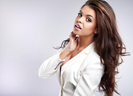 dishevel: Bella giovane donna con lunghi capelli modello Piuttosto marrone pone in studio