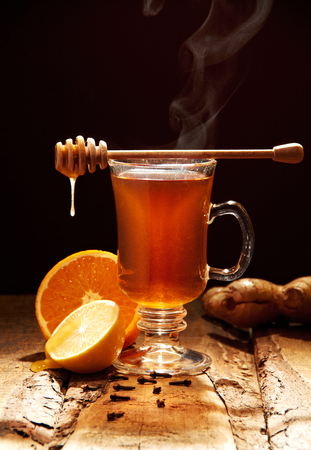 Winter tea with honey and orange on a wooden table photo
