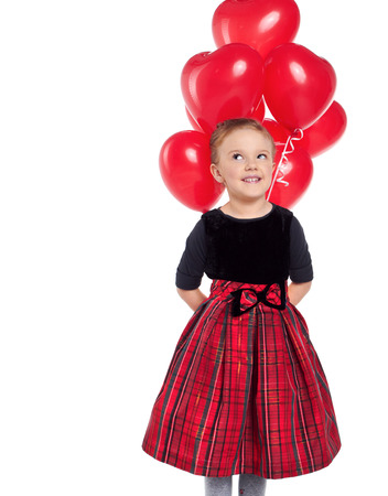 Cute little girl holding a bunch of red heart-shaped balloons  photo