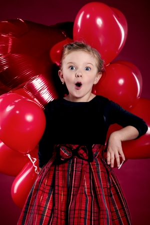 Surprised little girl holding a bunch of red heart-shaped balloons  photo