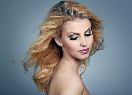 Beautiful young woman with blonde hair and evening make up photo