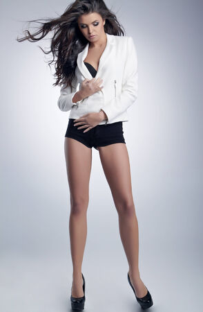 Sexy brunette woman in shorts and white jacket photo