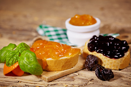 orange and plum jam with slices of bread on wooden table  photo
