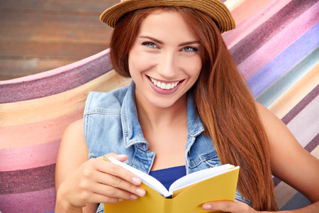 woman reading book: beautiful young woman resting in a hammock Stock Photo