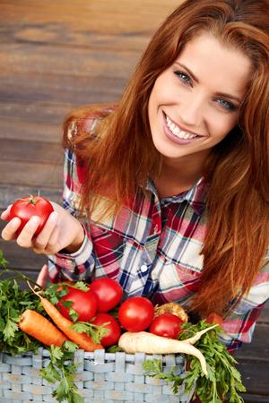庭で野菜を持つ美しい女性 写真素材