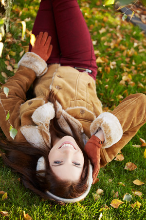 lies down: beautiful young woman in autumn park