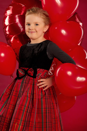 Smiling little girl holding a bunch of red heart-shaped balloons photo