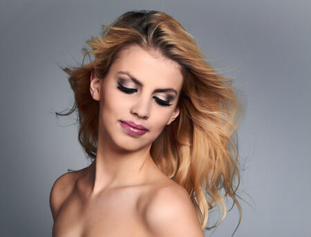 dishevel: Beautiful young woman with blonde hair. Pretty model poses at studio. Stock Photo