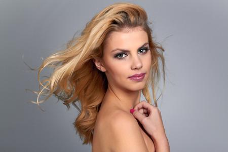 capelli biondi: Bella giovane donna con i capelli biondi. Modello grazioso pone in studio.