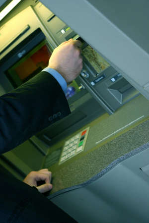 man puts in his card at an atm