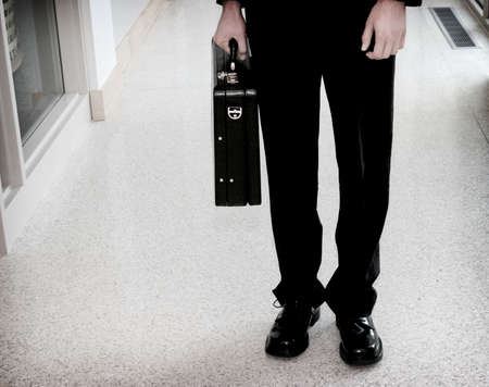 business man holding his briefcase and standing