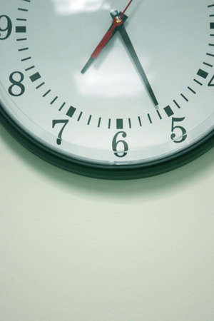 Business clock sits on the wall ticking Stock Photo