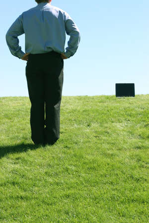 Business man standing near his laptop on a grassy hill
