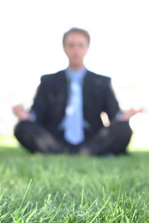 Business man sits on the green grass and meditates