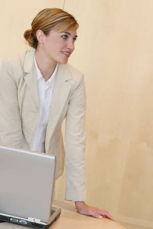 Business meeting and a business woman standing over her laptop