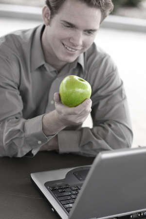 Business man holds a green apple in hand at lunch
