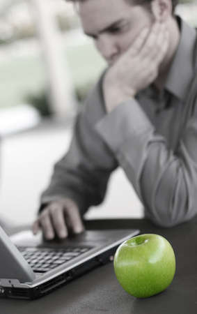 Business man works on his laptop with a green apple Imagens