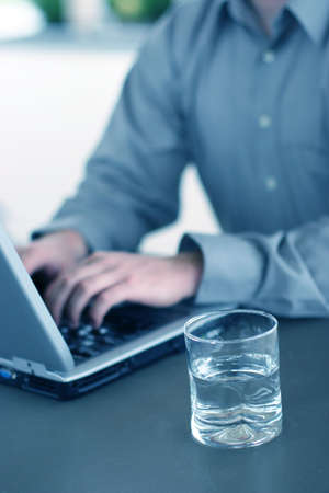 Casual business man works on his laptop with a glass of wate