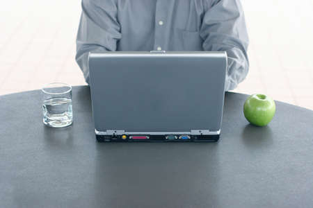 Business man sits at a table with water on his right and an apple on his left Stock Photo