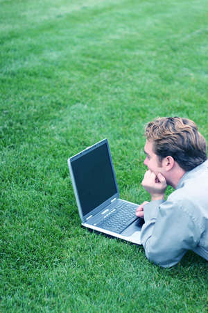 Business man looking at his computer screen in the park