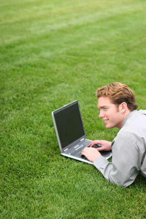 Cheerful business man works on his laptop in the green park Imagens