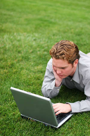 business man works on his laptop in the park
