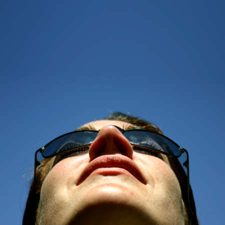 Woman in sunglasses looking up Stock Photo