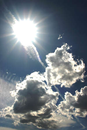 looming: Sun looming overhead of the clouds in a blue sky