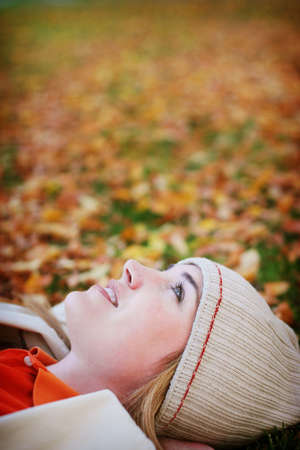 Young woman lays in the fall leaves