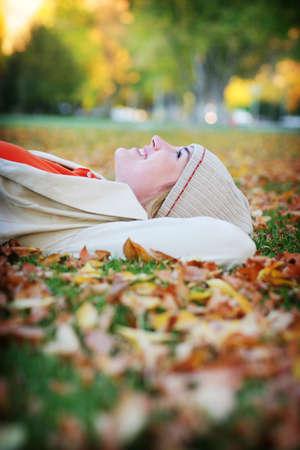 relaxes: Joven mujer se relaja en el oto�o las hojas