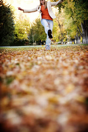 Young woman kicking up the leaves in the fall