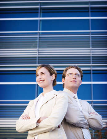 business man and woman standing together with arms folded Stock Photo