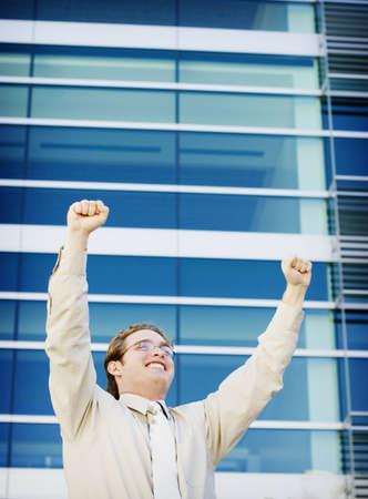 Business success as man raises arms
