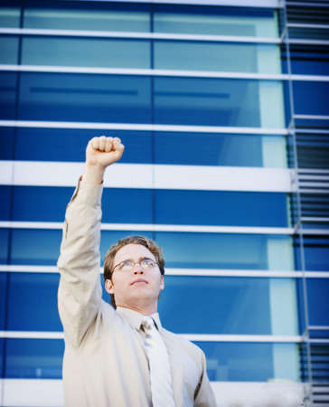 peo: Business man standing with arm raised Stock Photo