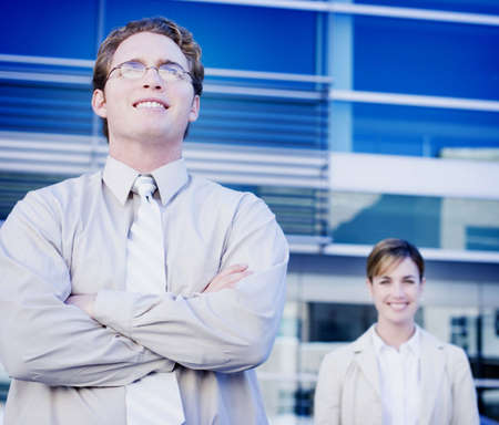 Business man standing in front of business woman and building Stock Photo