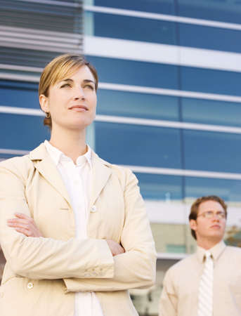 Business woman and man stand looking outward Stock Photo